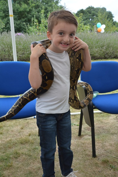 Supported sibling, Charlie, holds a boa constrictor