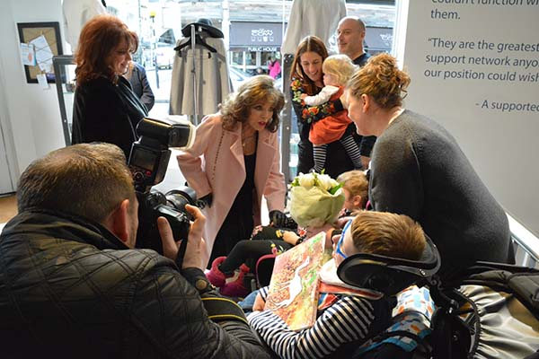 Dame Joan Collins greets supported families
