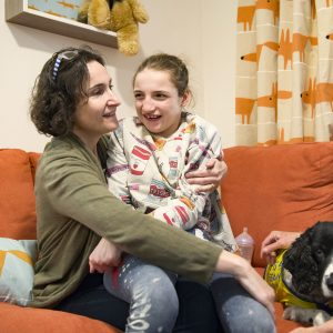Teenager girl sits with mum and Pets as Therapy dog