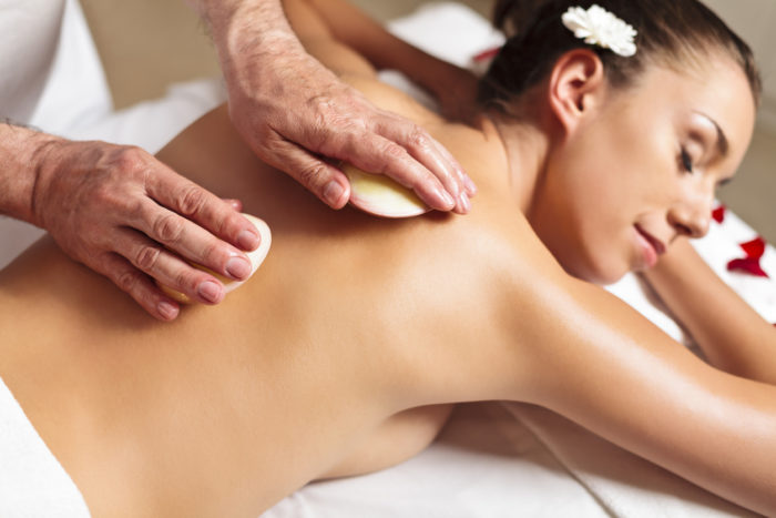 A relaxed woman receiving a lava shell massage